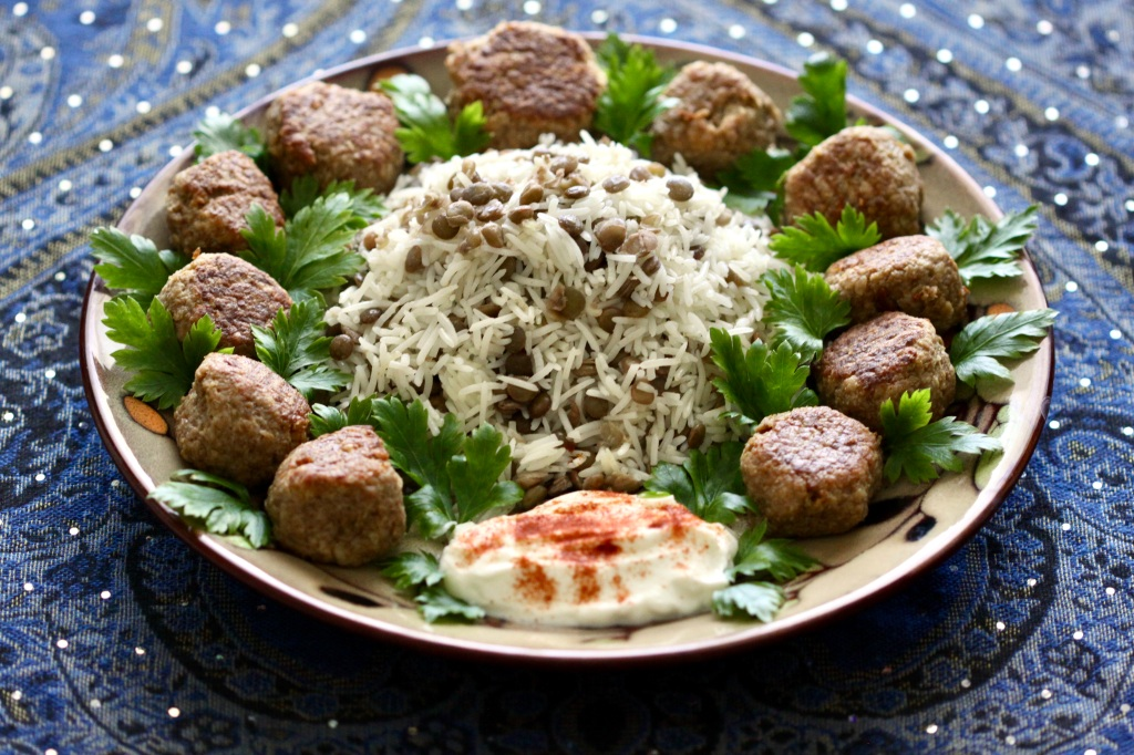 A plate of addas pilau and meatballs with parsley and paprika-adorned yogurt