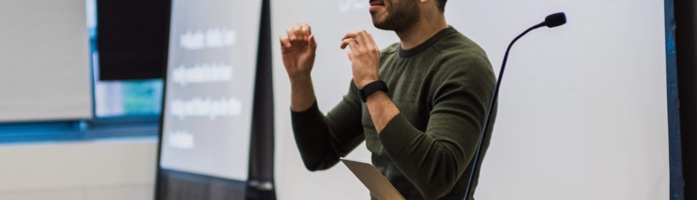 A man stands at a lectern. He is using American Sign Language.