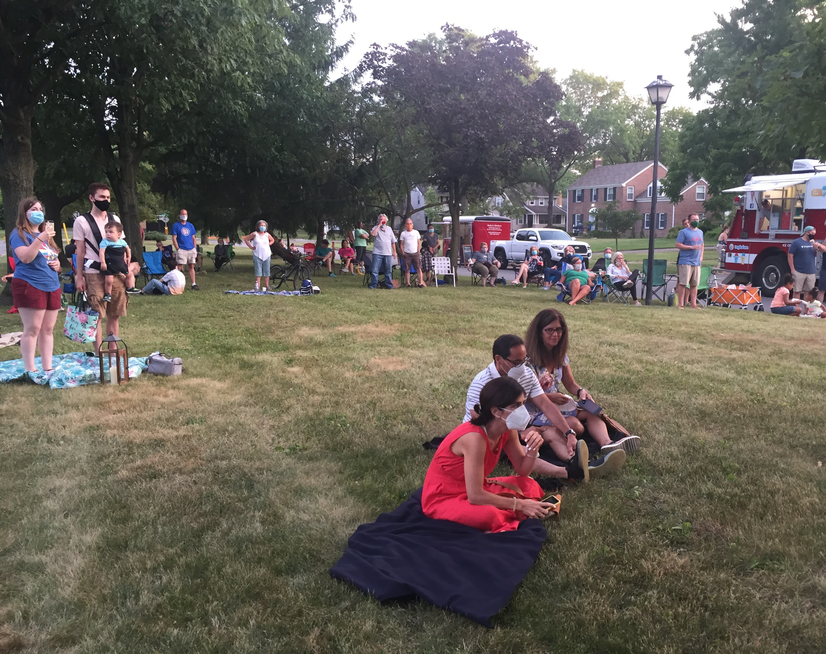 About twenty people stand and sit on a large lawn.