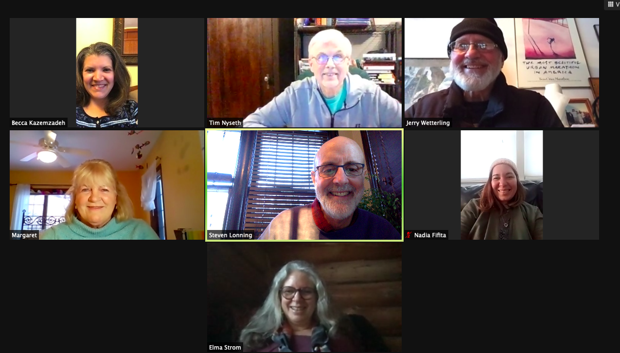 Seven people smile into their webcams on a video call.