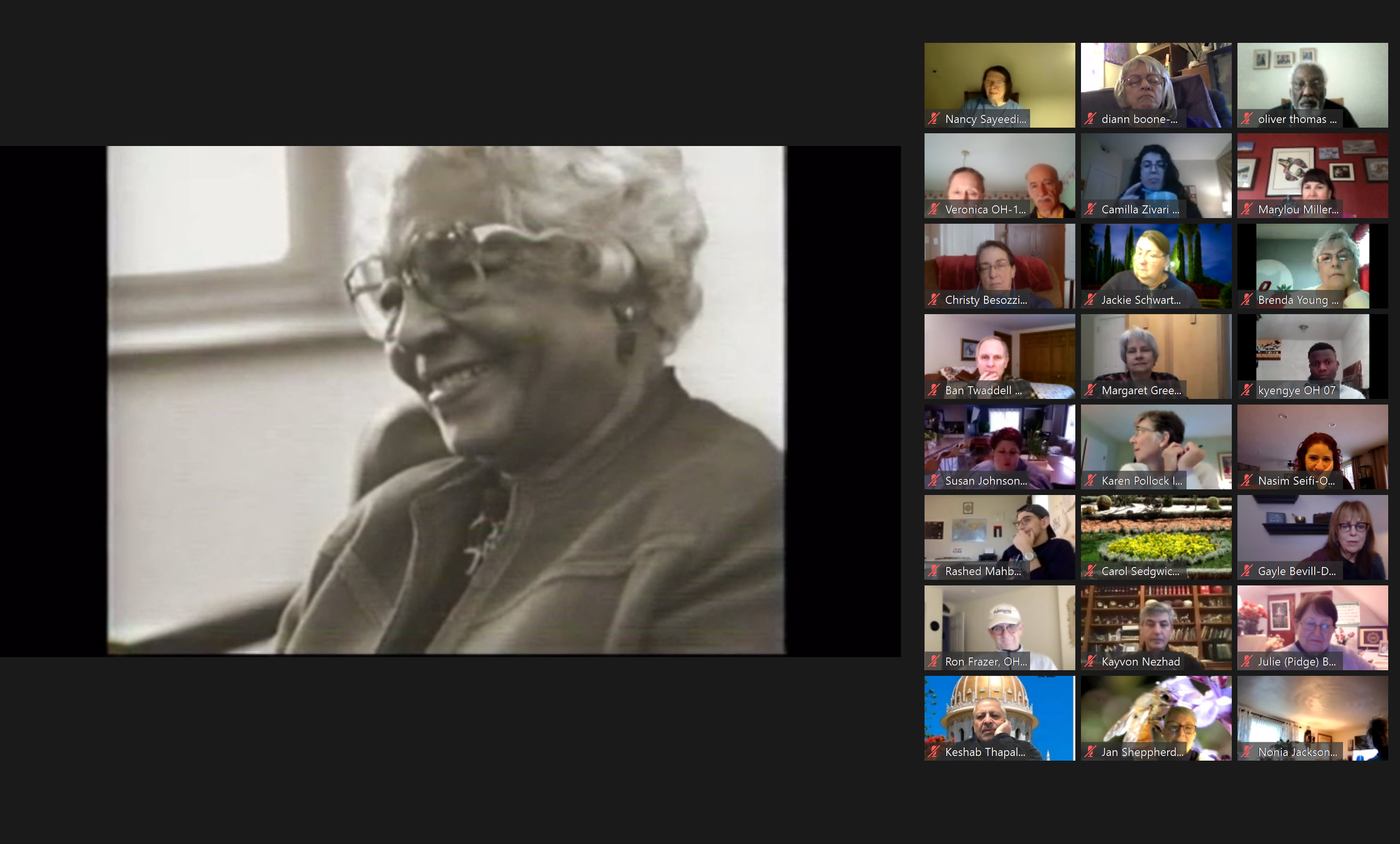 On a video call, about two dozen people look at an image of an elderly woman.