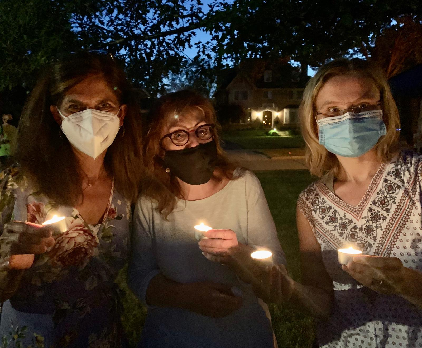 Three women hold candles at dusk. They wear face masks.